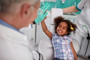 Lovely kid in dental chair with dentist satisfied after repairing teeth